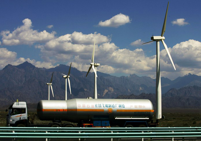 DABANCHENG, CHINA - SEPTEMBER 2: (CHINA OUT) A oil truck runs past wind turbines at the Dafancheng Wind Power Plant, the largest of its kind in Aisa, on September 2, 2007 in Dafancheng of Xinjiang Uygur Autonomous Region, China. Xinjiang is rich in wind resources and its installed capacity of wind generators is over 180,000 kilowatts. Xinjiang has been noted in ancient times along the old silk road as a political and commercial centre. It is the hub of an important commercial region, bordering Russia, Afghanistan, Kazakhstan, Tajikistan, Kyrgyzstan and Uzbekistan with Pakistan to its south. (Photo by China Photos/Getty Images)